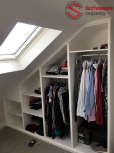 Photo of new loft wardrobe - doors open to show clothes hanging neatly